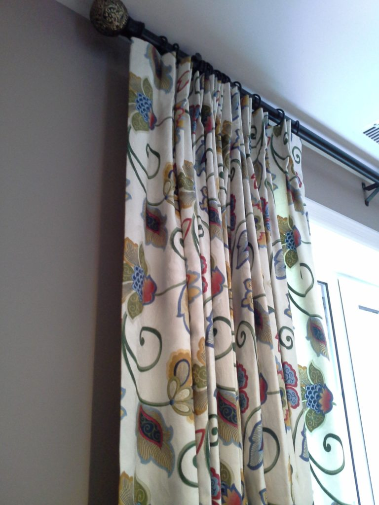 Traditional pleated draperies with bronzed rod and rings