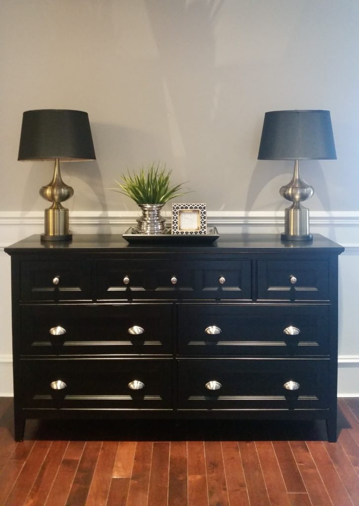Black dresser in front foyer with side lamps and accessories