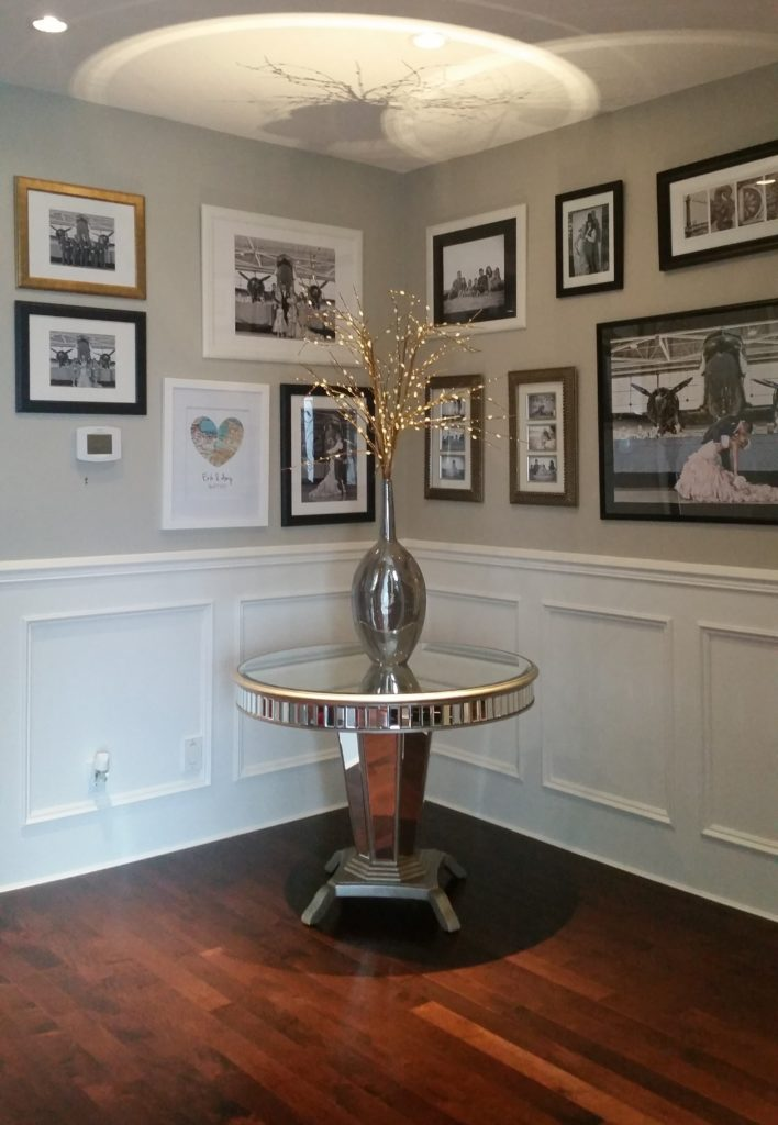 Foyer with wainscoting, family photo gallery and mirrored table with vase