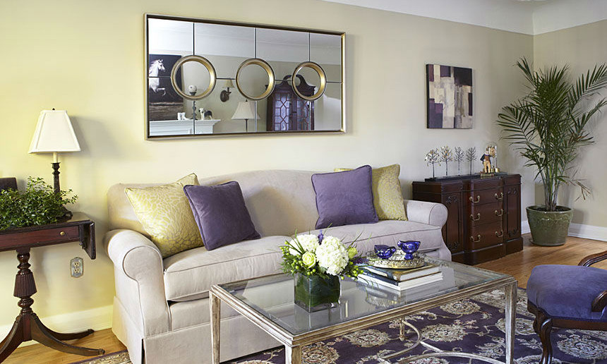 living-room-with-patterned-purple-area-rug-and-sofa-with-gold-and-purple-accent-pillows-and-mirror-with-circle-details-2