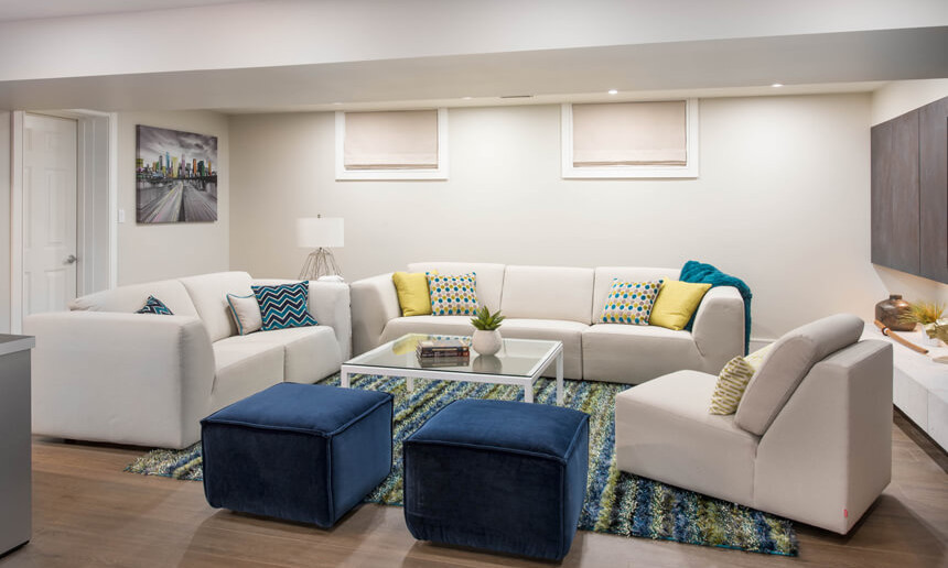 basement-living-room-with-white-and-blue-seating-and-blue-and-green-rug