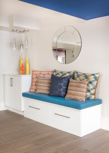 basement-seating-with-white-custom-cabinetry-and-blue-and-orange-pillows