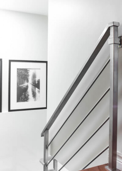 basement-staircase-with-stainless-steel-railings-and-artwork