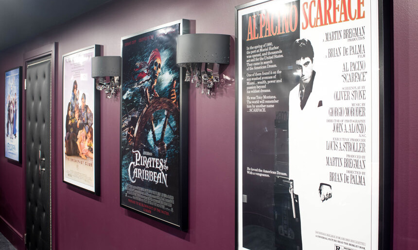 basement-theatre-with-movie-posters-and-light-sconces-on-purple-wall