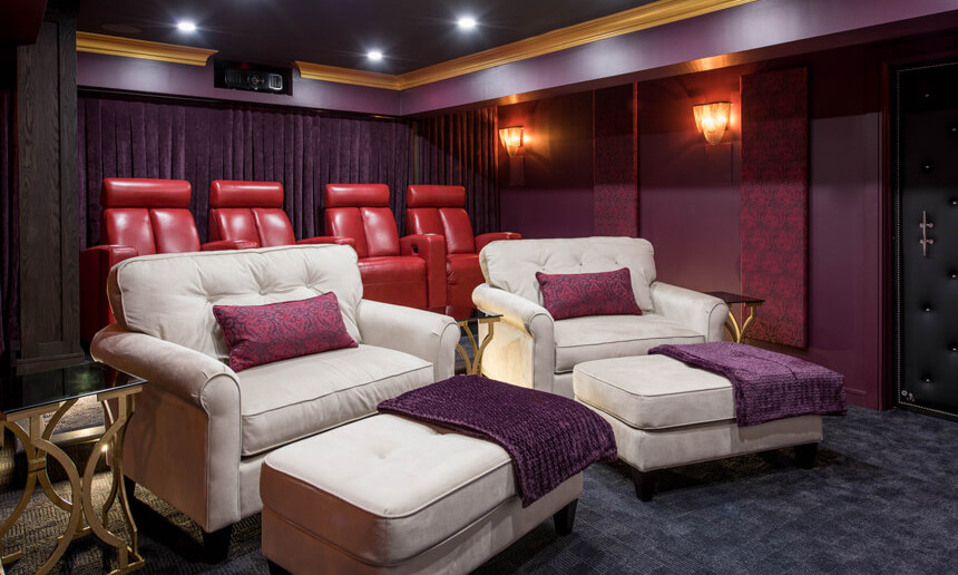 basement-theatre-with-purple-walls-and-large-white-chairs-and-red-movie-theatre-chairs