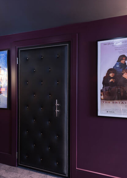 basement-theatre-with-sound-proof-door-and-purple-walls-with-movie-posters