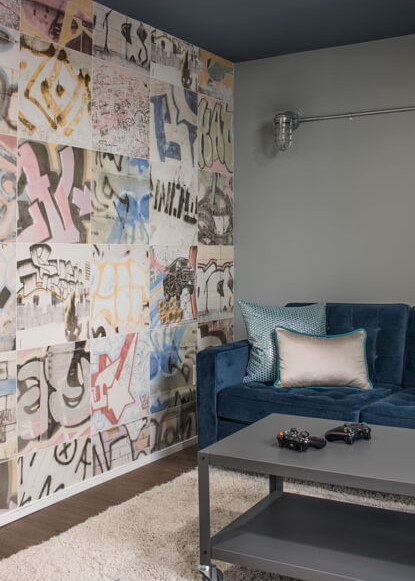 basement-with-graffiti-wall-art-and-blue-couch-and-coffee-table