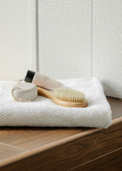 bathroom-accesories-on-wooden-shelf-with-white-towel-in-bathroom-design-2