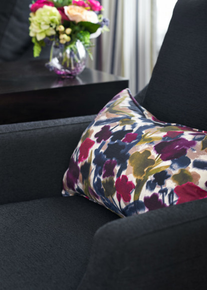 black-club-chair-with-bold-flowered-accent-cushion