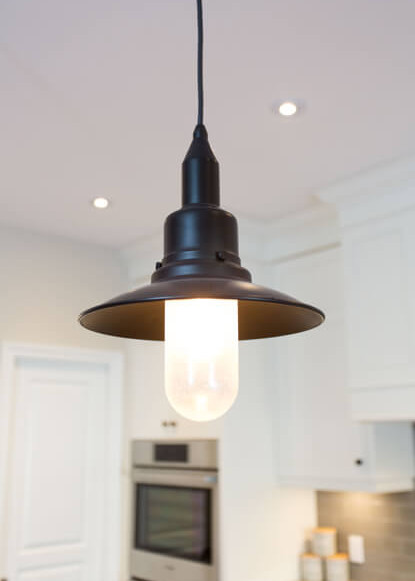 close-up-of-dark-pendant-lighting-in-traditional-kitchen-with-built-in-custom-cabinetry