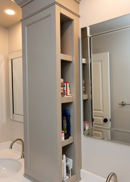 custom-cabinetry-with-hidden-shelving-for-his-and-her-sinks-and-bevelled-mirror-in-bathroom-design