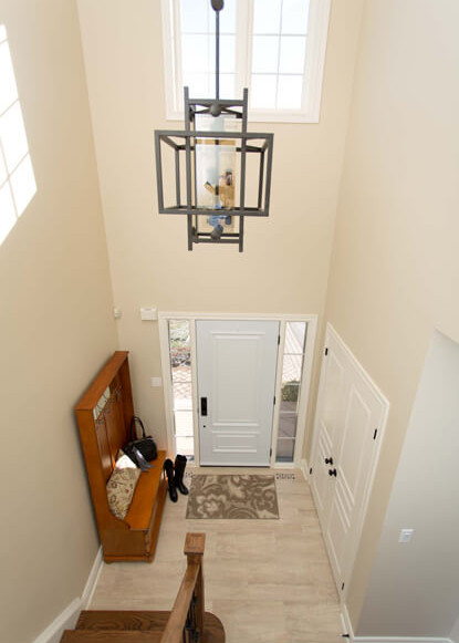 front-entry-foyer-with-white-doors-and-tiled-flooring-with-large-geometric-pendant-and-wooden-stairs