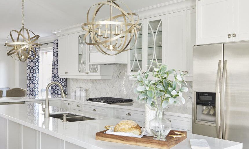 interior-kitchen-white-cabinetry-and-walls-with-stainless-steel-appliances-and-wooden-stools-herrigbone-backsplash-marble-white-quartz-countertops-and-hardwood-flooring-min