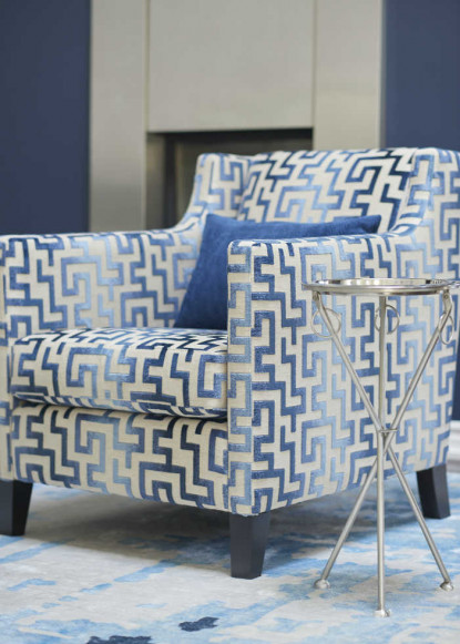 living-room-chair-with-blue-geometric-patterns-and-chrome-and-glass-side-table-on-blue-and-white-modern-rug-3