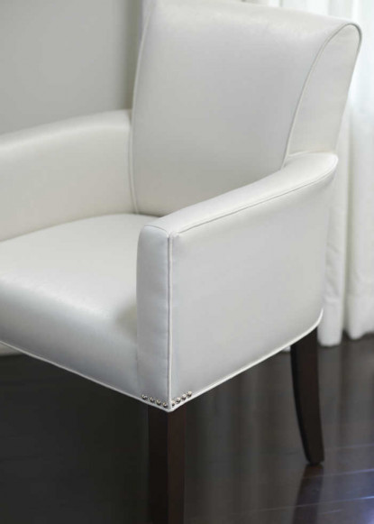 living-room-chair-with-nail-head-detail-and-white-leather-seat-on-dark-hardwood-floor-2