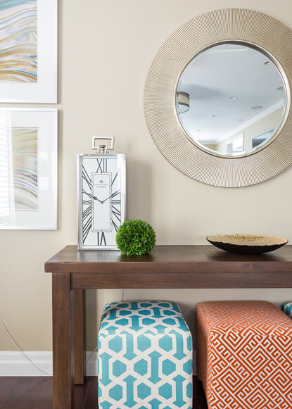 living-room-with-orange-and-teal-stools-and-renwil-mirror-and-artwork-with-consol