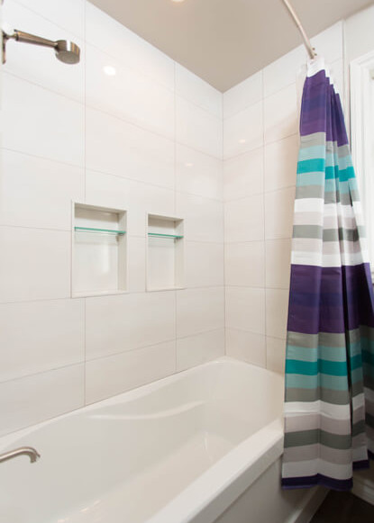 shower-bath-with-colourful-striped-shower-curtain-and-built-in-shelving-in-tiled-walls-and-shower-head