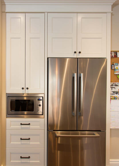 stainless-steel-fridge-built-in-to-custom-cabinetry-with-built-in-microwave-and-medium-dark-hardwood-flooring