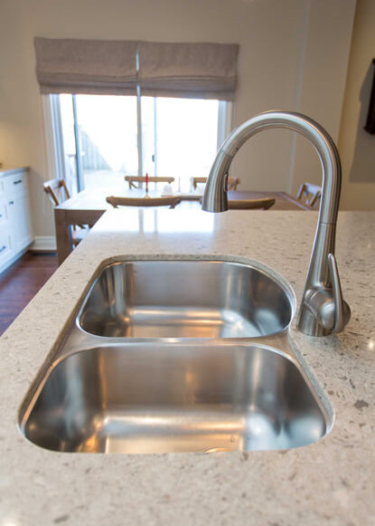 stainless-steel-undermount-sink-and-faucet-in-traditional-kitchen