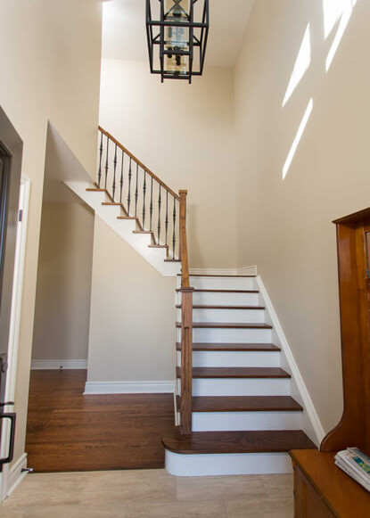 stairway-with-wooden-steps-and-rail-contrasting-with-tile-flooring-and-large-geometric-pendant-light