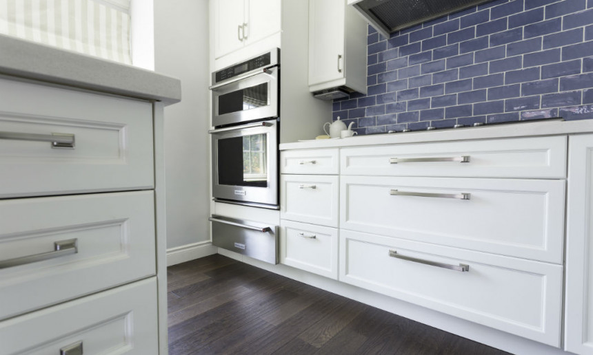 traditional-kitchen-with-custom-white-cabinetry-built-in-stainless-steel-wall-ovens-blue-subway-tile-backsplash-and-dark-hardwood-flooring