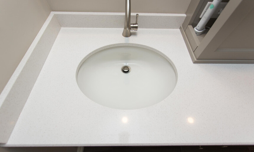 white-countertop-and-polished-faucet-and-white-undermount-sink-in-bathroo-with-custom-cabinetry-and-hidden-shevlving
