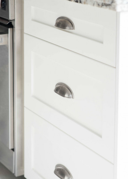 white-custom-drawers-in-kitchen-with-stainless-steel-appliances-and-close-up-of-hardware
