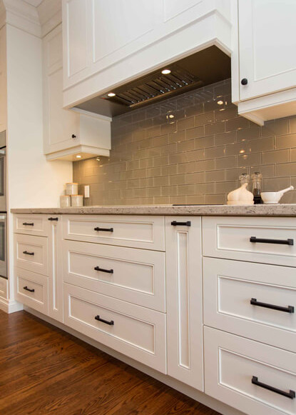 white-kitchen-with-custom-cabinetry-and-dark-hardwood-floors-with-painted-glass-backsplash-subway-tile