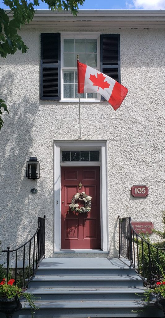White Stucco House Burgundy Front Door Canada Flag